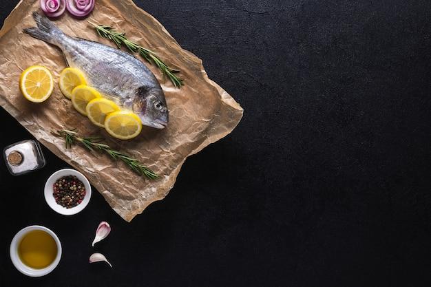 Rauwe verse dorado-vis op kookpapier bereid om te koken met kruiden op een zwarte achtergrond. zeevruchten. bovenaanzicht. ruimte kopiëren.