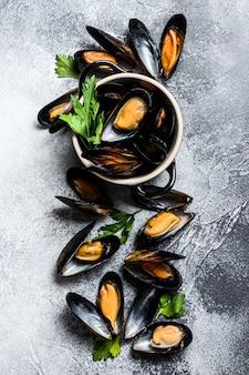 Rauwe verse mosselen in schelpen. het concept van het koken van zeevruchten. grijze muur. bovenaanzicht