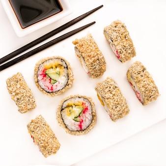 Rauwe verse sushi roll met sojasaus in witte plaat, japanse voedselstijl. geassorteerde sushi ingesteld op witte betonnen achtergrond. japanse sushi, broodjes, sojasaus, eetstokjes. bovenaanzicht. verschillende sushi gemengd