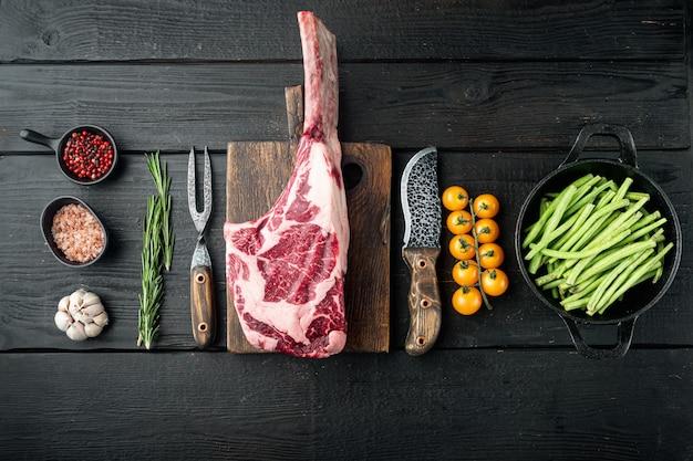 Rauwe verse tomahawk droge leeftijd gemarmerde biefstuk set, met ingrediënten van de grill, op zwarte houten tafel