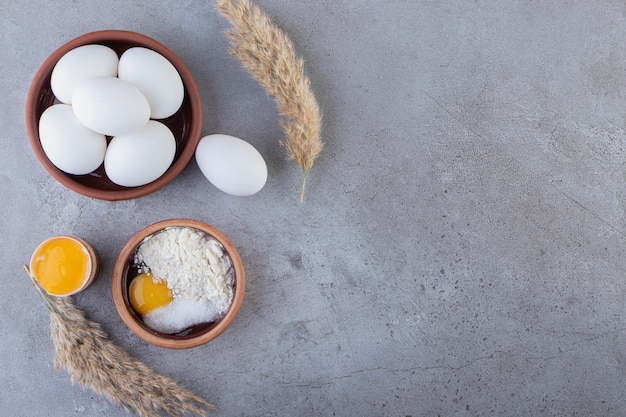 Rauwe verse witte kippeneieren geplaatst op een stenen oppervlak.
