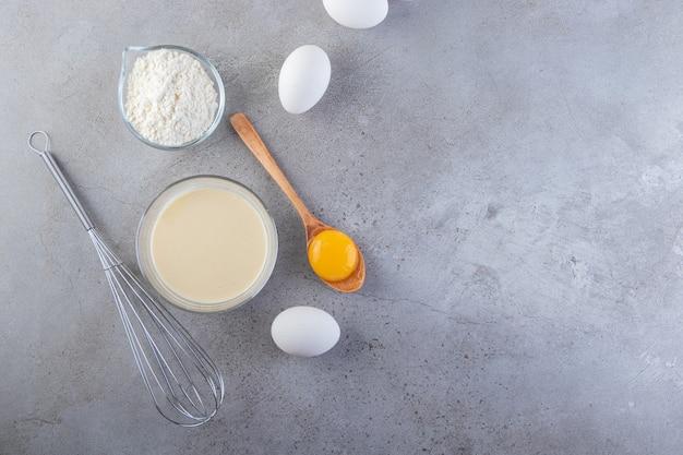 Rauwe verse witte kippeneieren met melk en bloem.