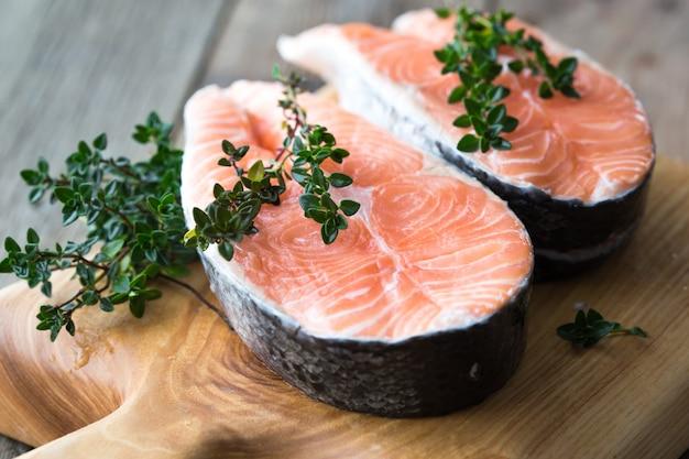Rauwe, verse zalm steak op een bord en specerijen rond. rauwe zalm rode vis. kokende zalm, zeevruchten. gezonde voeding concept. zalm en kruiden