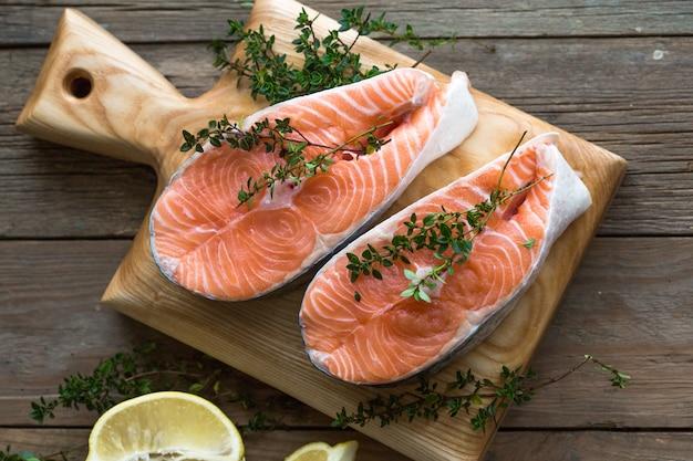Rauwe, verse zalm steak op een houten bord en specerijen rond. rauwe zalm rode vis. kokende zalm, zeevruchten. gezonde voeding concept. zalm en kruiden