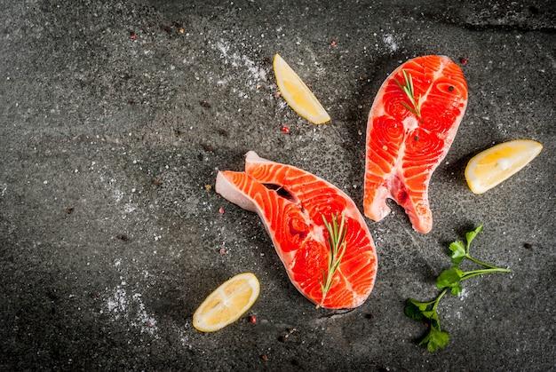 Rauwe verse zalm vis met ingrediënten voor het koken van olijfolie, citroen, ui, peterselie, rozemarijn, op zwarte stenen tafel, copyspace bovenaanzicht