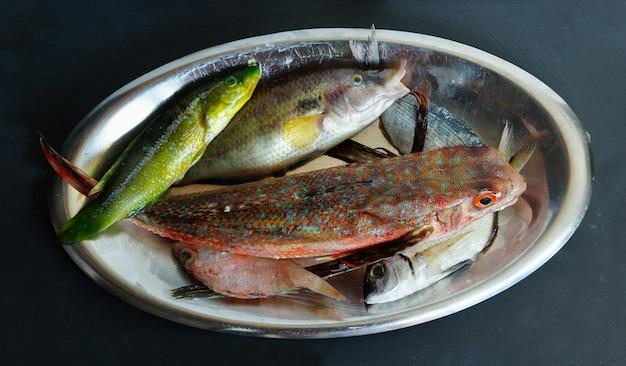 Rauwe verse zeevis kleurrijk op het zwarte leisteen bureau