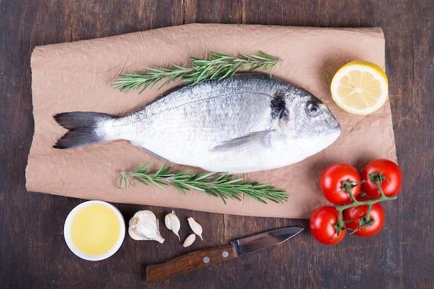 Rauwe vis dorado koken en ingrediënten. dorado, citroen, tomaat, kruiden en specerijen. bovenaanzicht op houten tafel