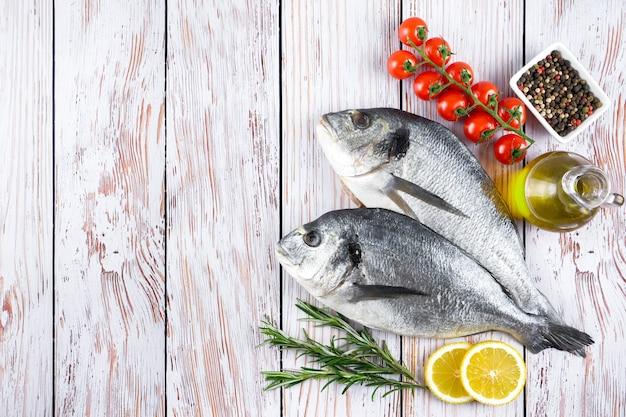 Rauwe vis dorado op witte houten achtergrond met kruiden, tomaat, rozemarijn, olijfolie en citroen. bovenaanzicht, plat gelegd met kopieerruimte voor tekst