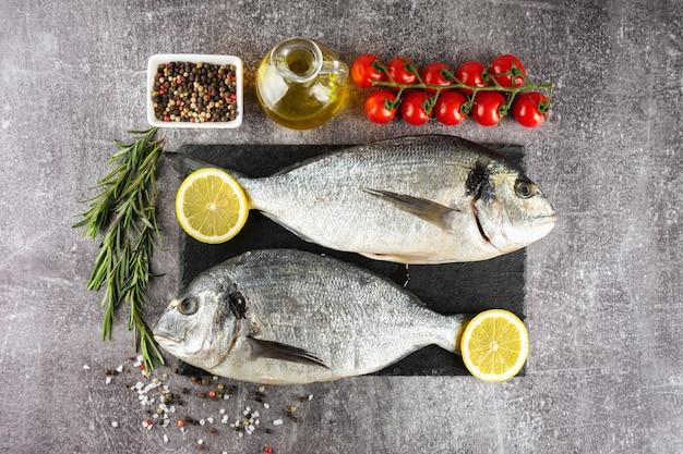 Rauwe vis dorado op zwarte leisteen snijplank en grijze betonnen ondergrond met kruiden, tomaat, rozemarijn, olijfolie en citroen. bovenaanzicht, plat gelegd met kopieerruimte voor tekst