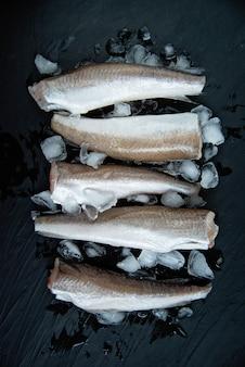 Rauwe vis heek. vijf rauwe visfilet op ijs op donker,