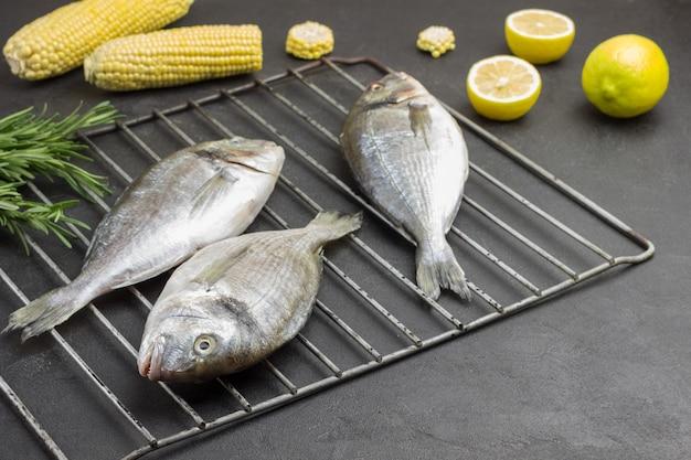 Rauwe vis met maïs en citroen op de grill. takjes rozemarijn.