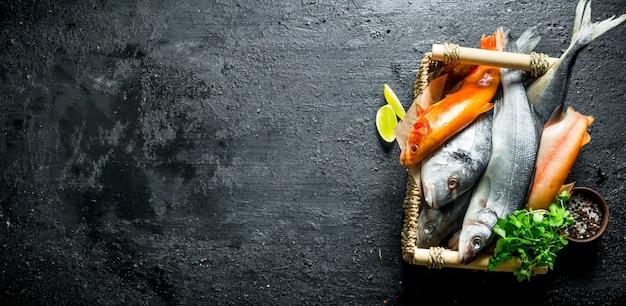 Rauwe vis op dienblad met peterselie en limoenplakken. op zwarte rustiek