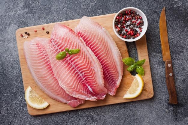 Rauwe visfilet van tilapia op een snijplank met citroen en kruiden. donkere tafel