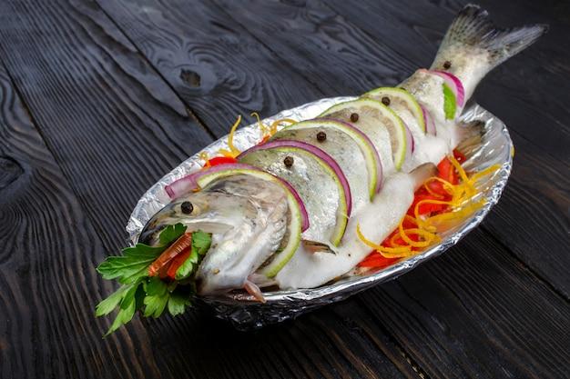 Rauwe visforel gekookt voor het koken met citroen en tomaten op een bord met folie.