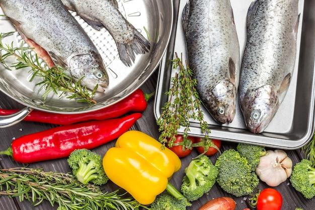 Rauwe visforel met groenten in koekenpan en metalen dienblad. bloemkool, kikkererwten, rozemarijn en citroen, champignons en paprika. plat leggen