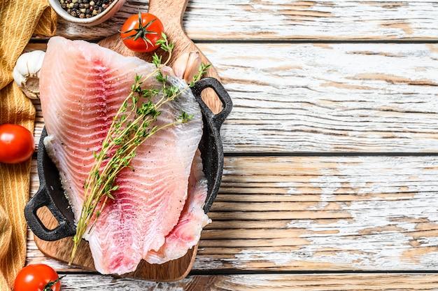 Rauwe vissentilapia in een pan op houten wit