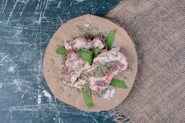 Rauwe vleesstukken met verse en gedroogde kruiden op blauw.