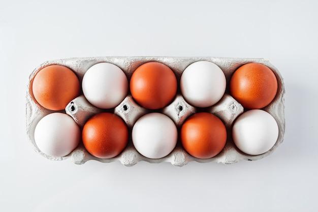 Rauwe witte en bruine kippeneieren in een milieuvriendelijke kartonnen doos op een lichte achtergrond