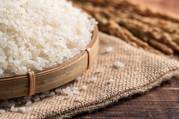 Rauwe witte gepolijste gemalen eetbare rijst op houten tafel achtergrond in een kom, biologisch ontwerpconcept.
