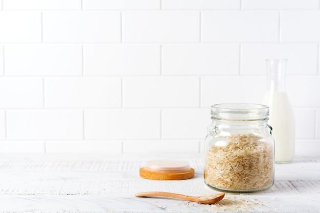 Rauwe witte rijstvariëteit arborio voor italiaanse risottogerechten in glazen pot op witte betonnen of stenen achtergrond. selectieve aandacht. ruimte kopiëren.