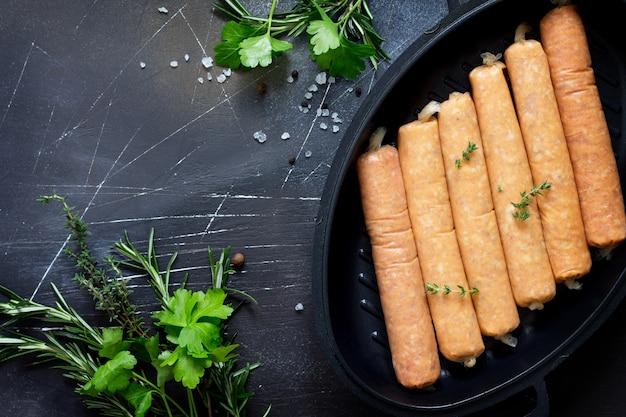 Rauwe worst op een gietijzeren grillpan met kruiden en specerijen op een donkere stenen ondergrond picnic