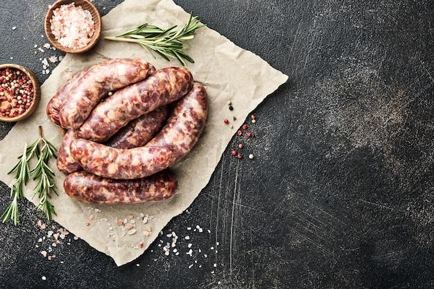 Rauwe worsten of braadworst en ingrediënten voor het koken op donkere stenen achtergrond. bovenaanzicht met kopie ruimte.