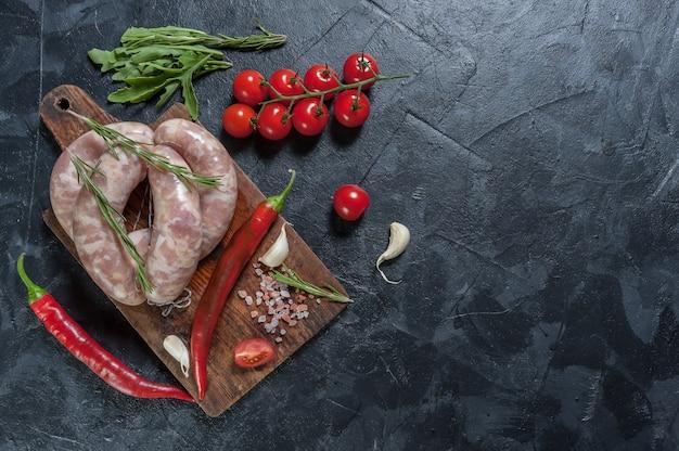 Rauwe worstjes op snijplank, chili en tomaten