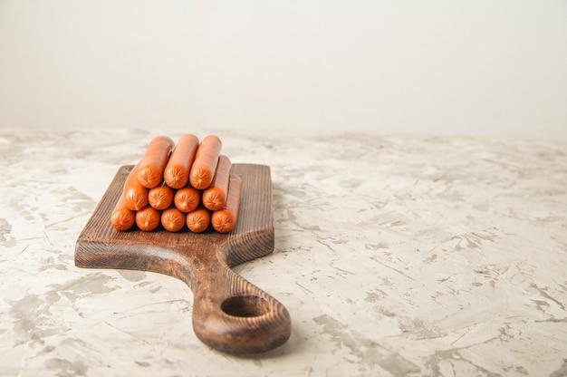 Rauwe worstjes uit de winkel op een houten plank en kopieer de ruimte.