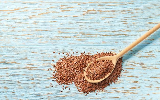Rauwe zaden van vlas in een houten lepel op een blauwe houten tafel