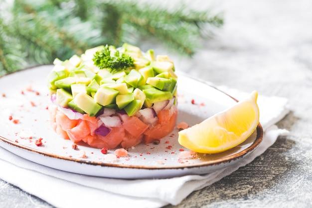 Rauwe zalm, avocado en paarse uiensalade. zalmtartaar. voorgerecht voor oudejaars of kersttafel