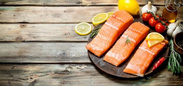 Rauwe zalm visfilet met citroen, tomaten en kruiden op rustieke tafel.