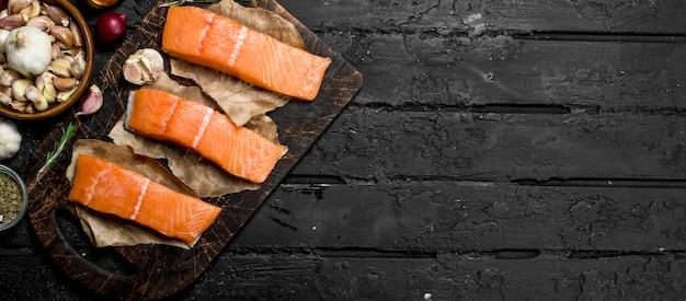 Rauwe zalm visfilet met kruiden op rustieke tafel.