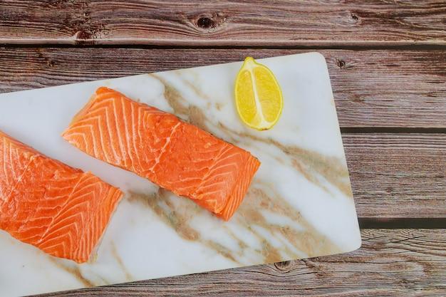 Rauwe zalm visfilet met plakjes citroen op een marmeren bord