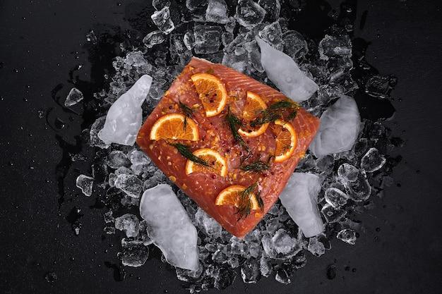 Rauwe zalmfilet met stukjes sinaasappel op stukjes ijs op een zwarte achtergrond