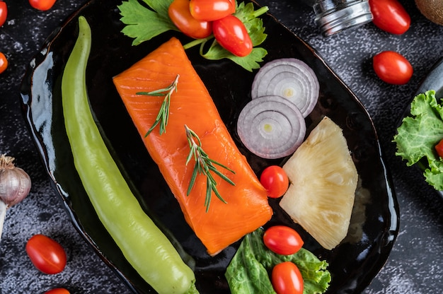 Rauwe zalmfilets, peper, kiwi, ananas en rozemarijn op een bord en zwarte cementvloer.