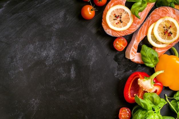 Rauwe zalmlapjes vlees en verse ingrediënten voor het koken op een donkere achtergrond.