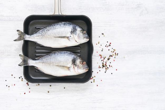 Rauwe zeebrasem vissen in pan. bovenaanzicht, kopieer ruimte. mediterraan zeevruchtenconcept.