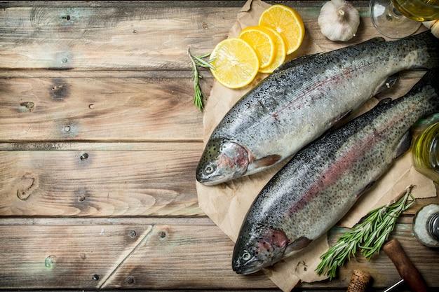 Rauwe zeevis zalm op oud papier met plakjes citroen en geurige rozemarijn. op houten achtergrond