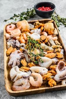 Rauwe zeevruchten mix in een houten kom. grijze achtergrond. bovenaanzicht