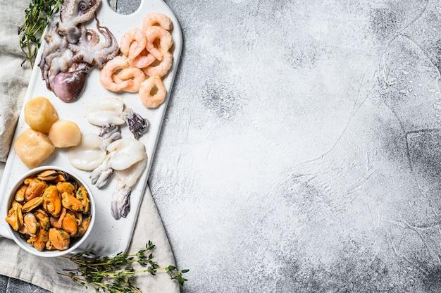 Rauwe zeevruchten zee cocktail op keramische snijplank. grijze achtergrond. bovenaanzicht. ruimte voor tekst