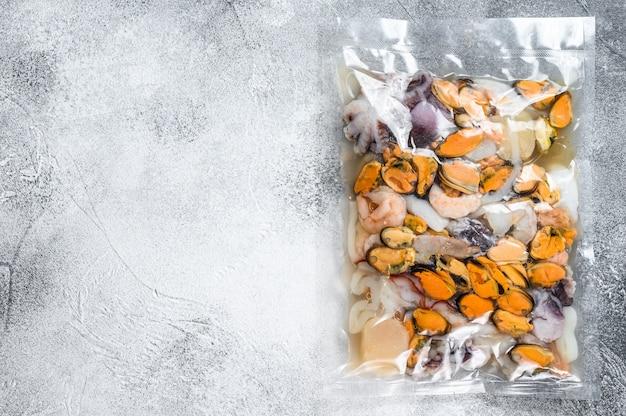 Rauwe zeevruchtenmix in vacuümverpakking. grijze achtergrond. bovenaanzicht. ruimte voor tekst