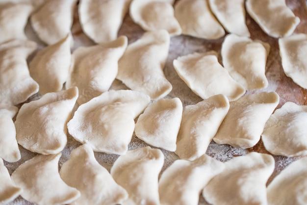 Rauwe zelfgemaakte dumplings op houten achtergrond close-up.