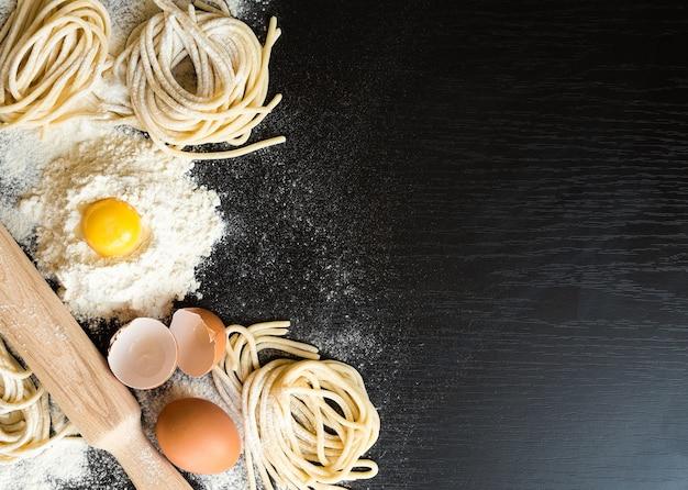 Rauwe zelfgemaakte pasta met ingrediënten op zwarte achtergrond. bovenaanzicht.