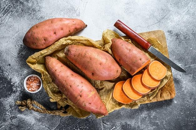 Rauwe zoete aardappelen op een snijplank, biologische yam. farm groenten. grijze achtergrond