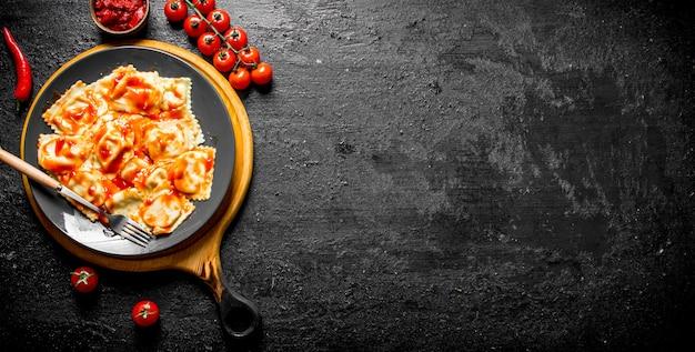 Ravioli met kerstomaatjes en saus. op zwarte rustieke tafel