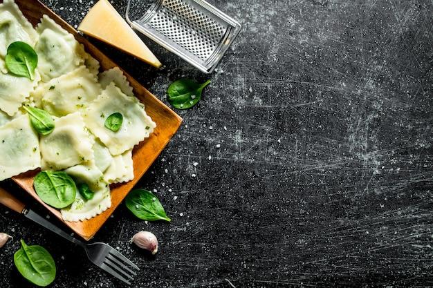 Ravioli met knoflook, kaas en spinazie. op donkere rustieke ondergrond