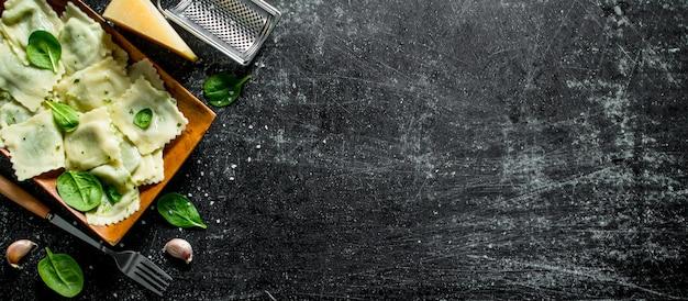 Ravioli met knoflook, kaas en spinazie. op donkere rustieke tafel