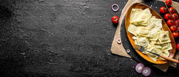 Ravioli met tomaten, saus en uienringen. op zwarte rustiek