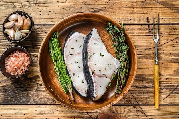 Raw blue shark biefstuk in een houten plaat houten tafel. bovenaanzicht.
