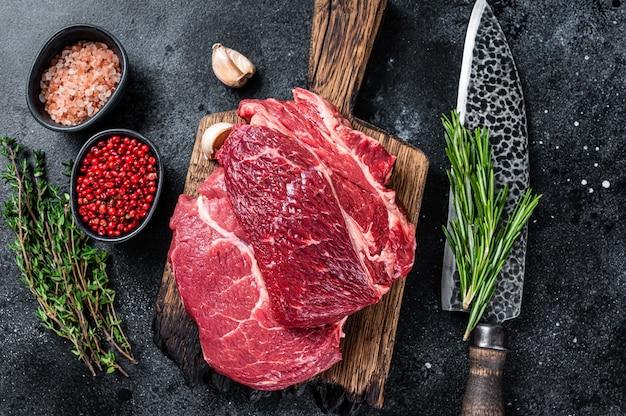 Raw chuck eye roll black angus prime biefstuk op slagersbord met mes